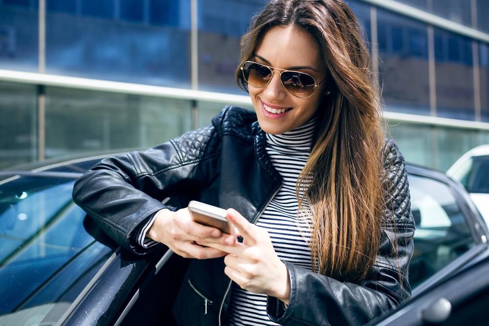 La calidad laboral en Nueva Zelanda - Mujer joven sonriendo mirando el movil - theinfinitynz