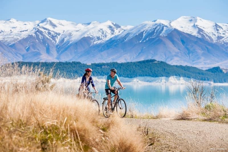 Inmigración en la Skilled Migrant Visa de Nueva Zelanda. Pareja montando en bicicleta por la montaña en Nueva Zelanda