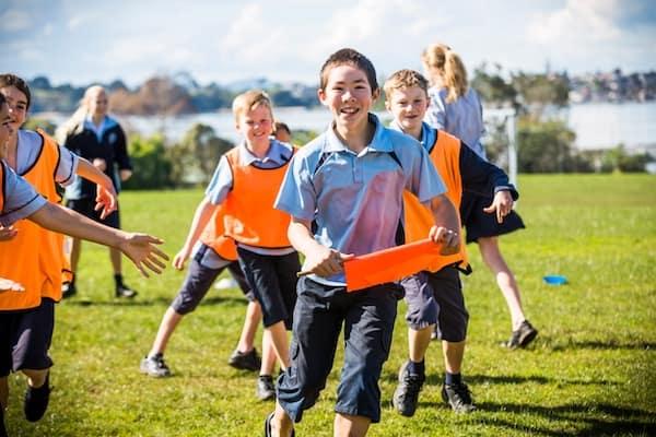 Alumnos jugando en el campo de deportes en un colegio en Nueva Zelanda.