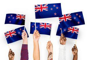 6 razones para emigrar a Nueva Zelanda. Seis manos sujetando 6 banderas de bienvenidos a Nueva Zelanda